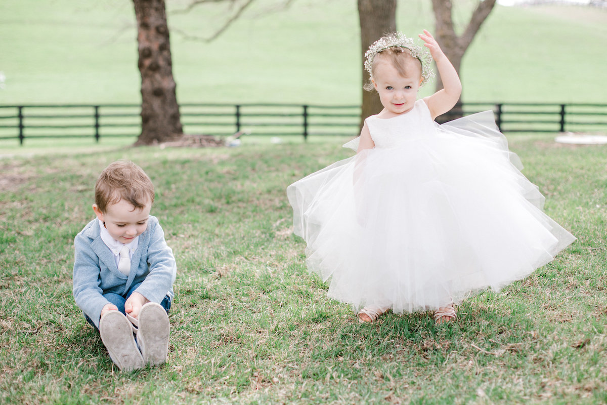 ring_bearer_and_flower_girl_in_big_dress_playing_in_grass.jpg