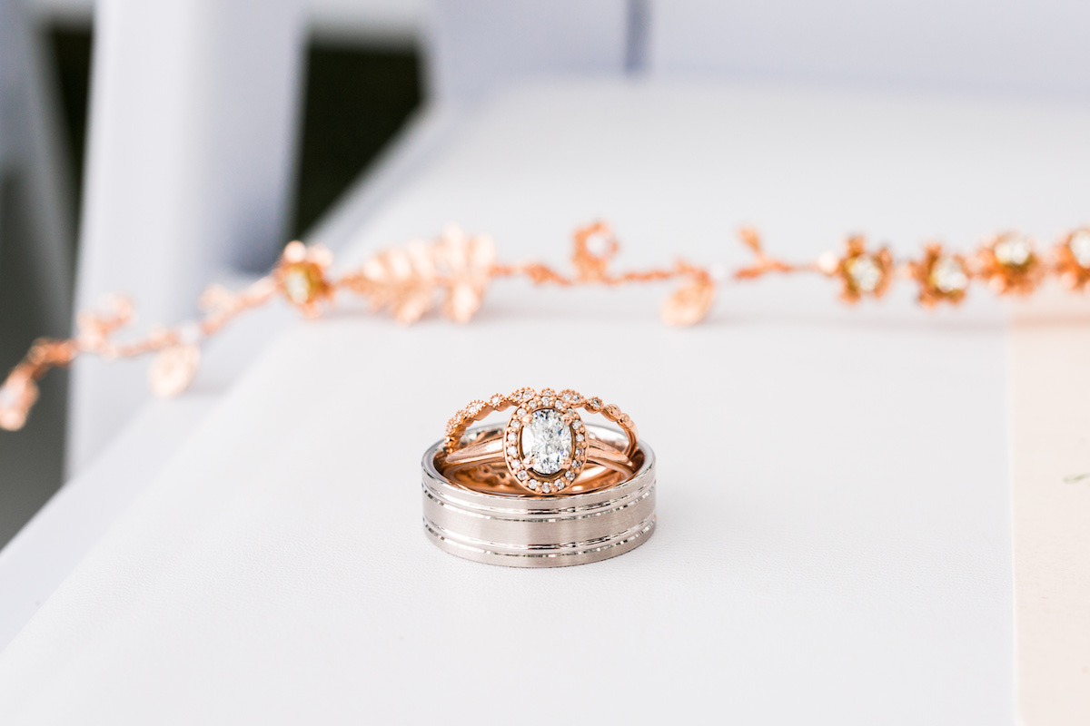 rose_gold_diamond_ring_and_wedding_bands_on_white_table.jpg