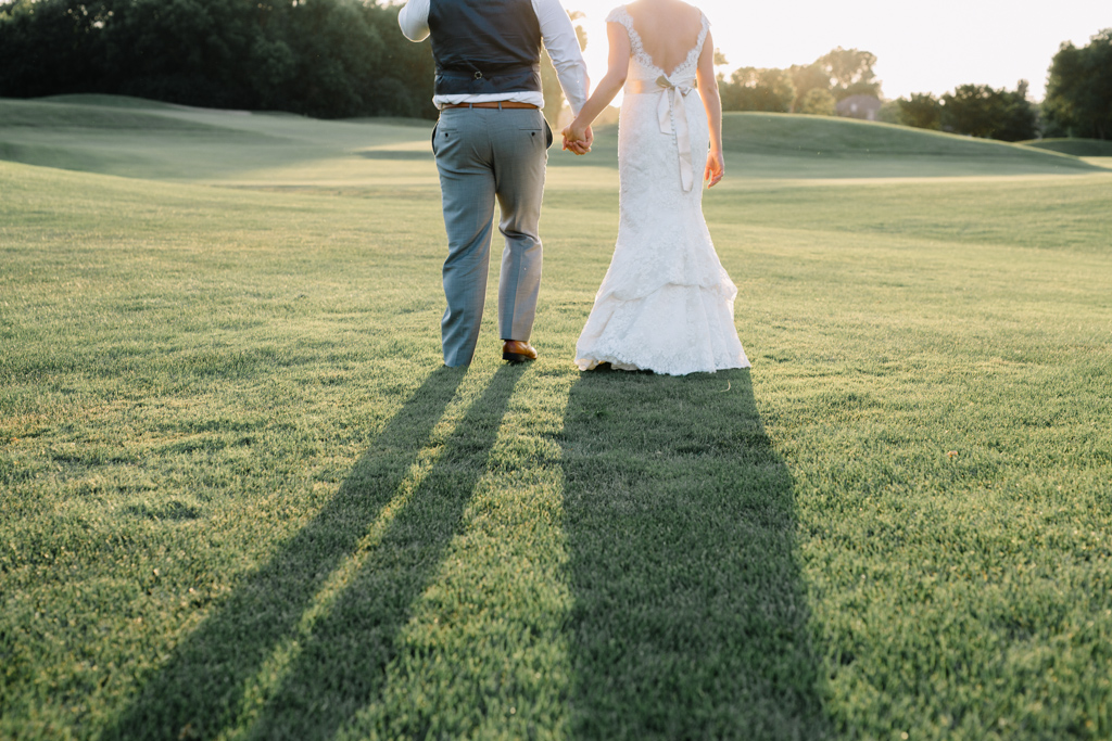shadows_bride_and_groomo_holding_hands_golf_course.jpg