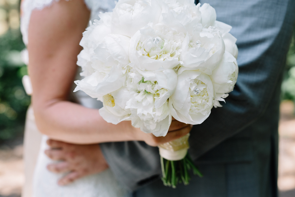side_angle_of_white_rose_bouquet_couple_hugging.jpg