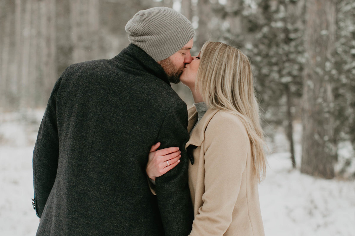 sideways_kiss_between_couple_in_winter_forest.jpg