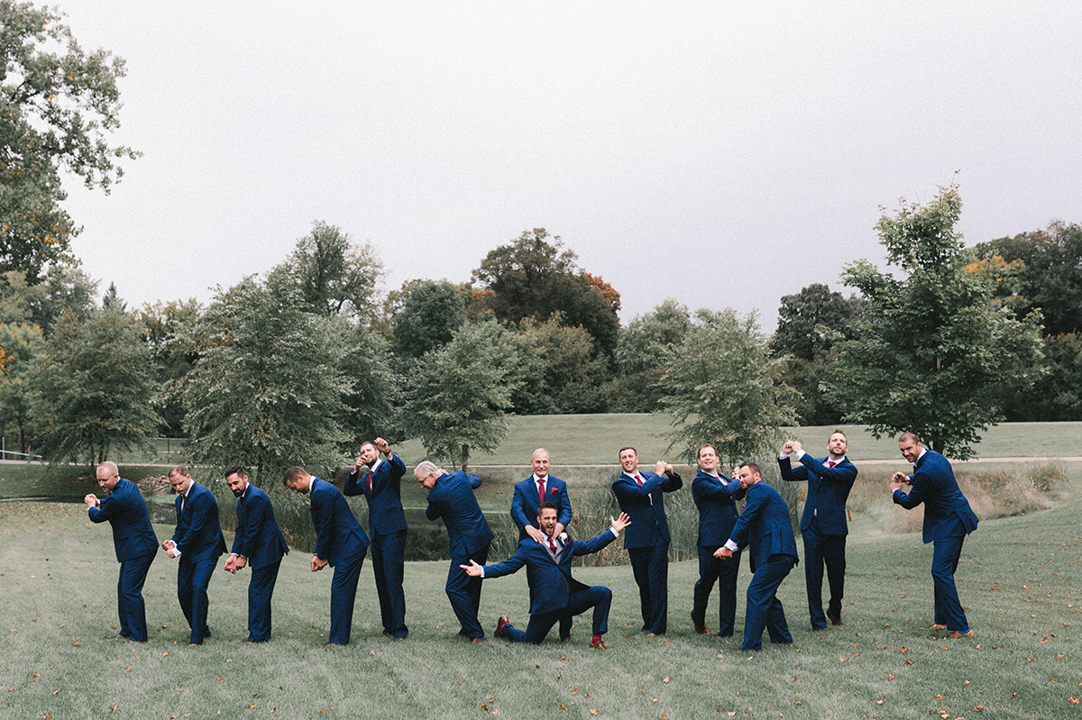silly_groomsmen_striking_poses_navy_suits.jpg