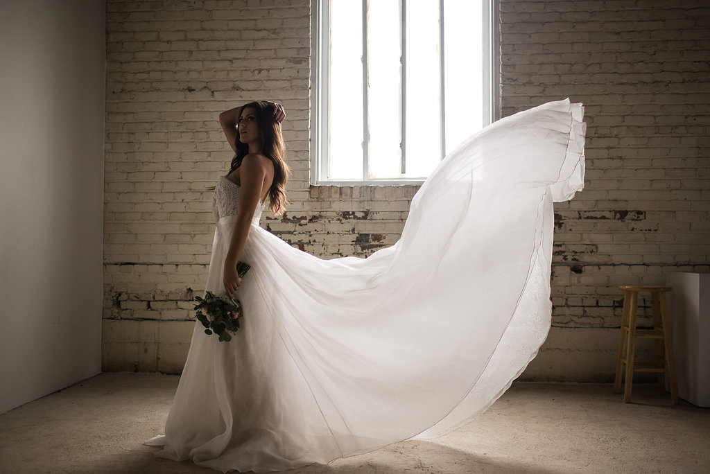 stunning_bride_standing_dress_train_blowing_in_wind.JPG