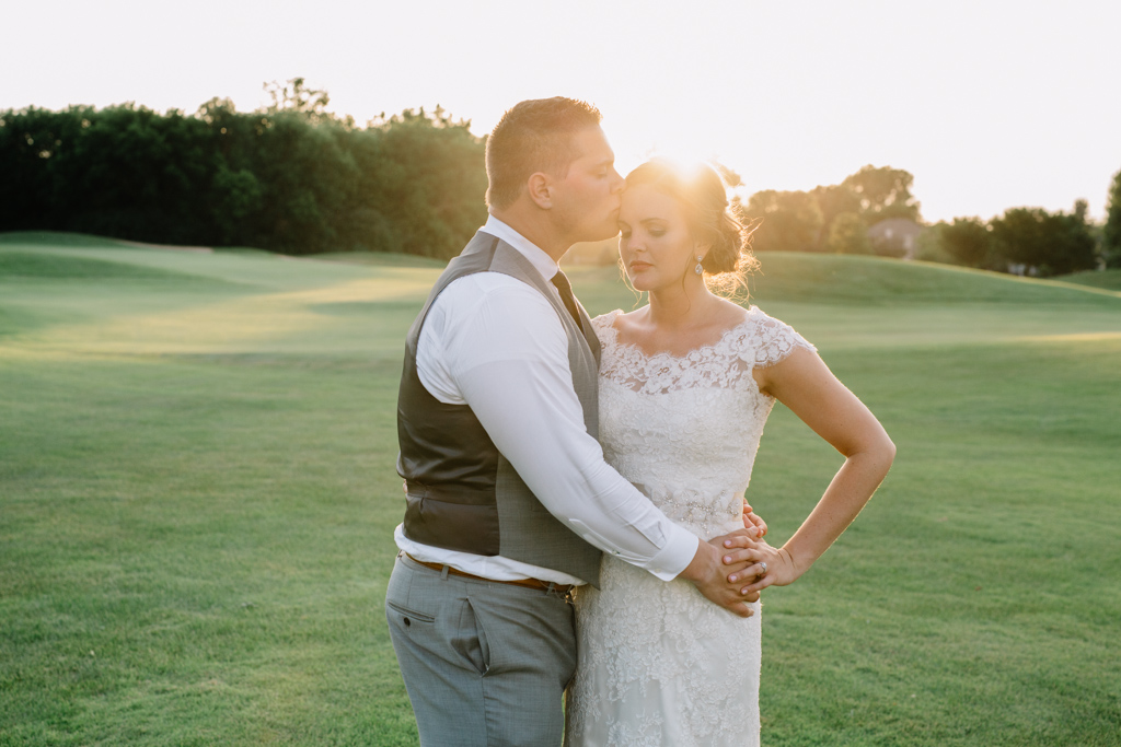 sunset_golf_course_wedding_groom_kissing_brides_forehead_hand_on_hip.jpg
