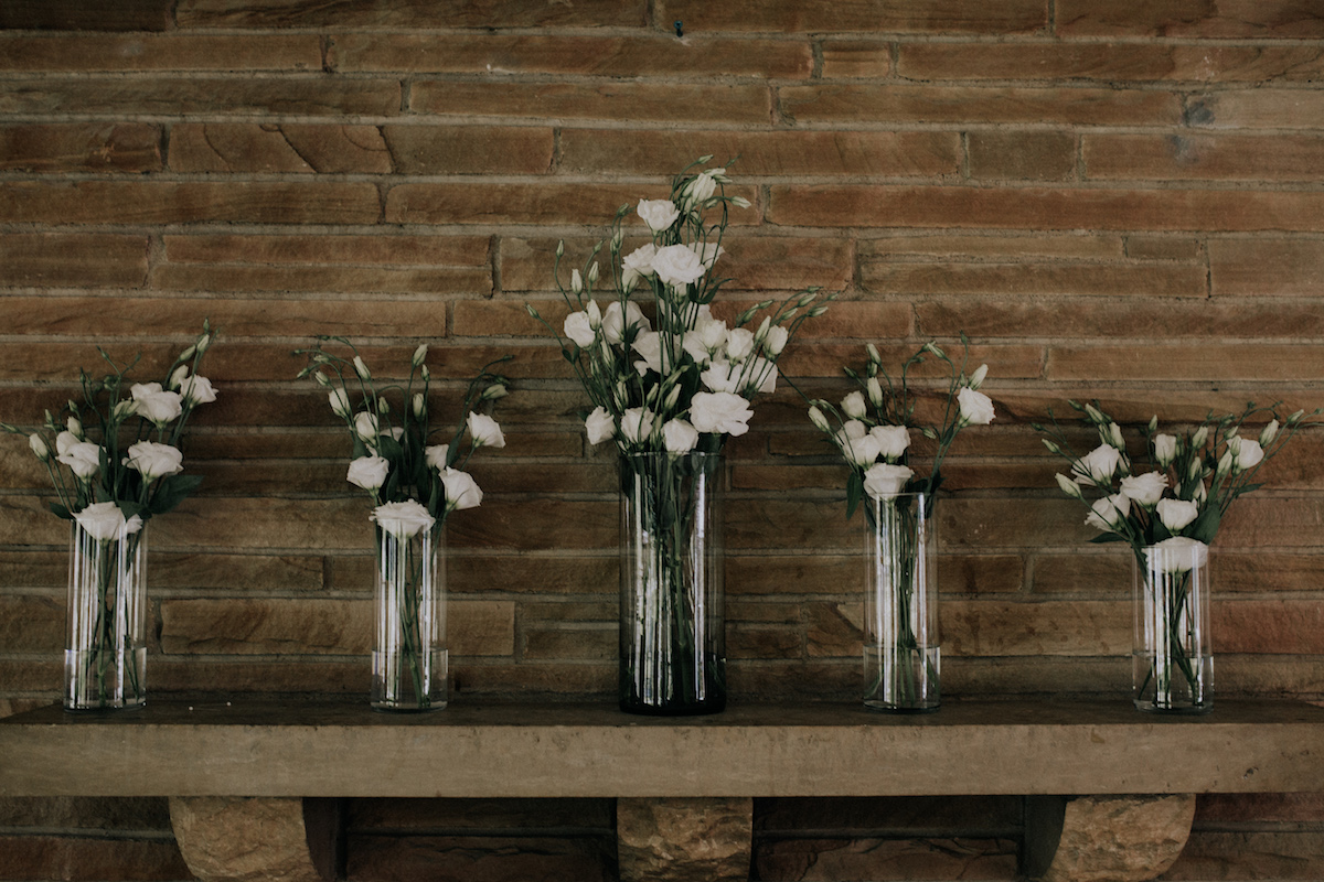 tall_glass_vases_with_white_flowers_against_brown_brick.jpg