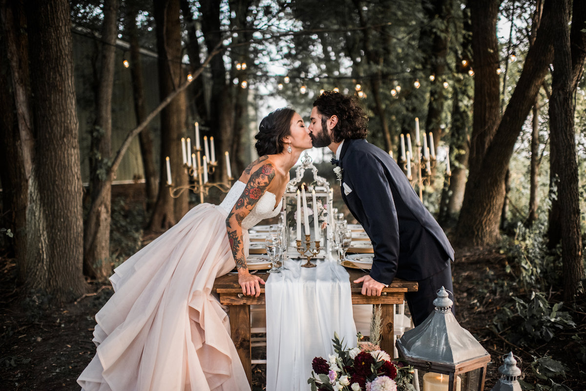 tattoo_bride_and_groom_kiss_over_table_in_magical_forest.jpg