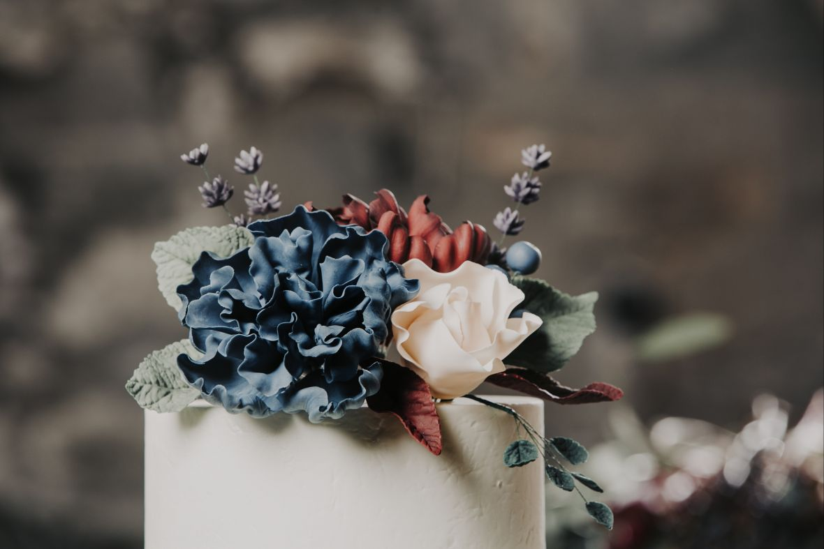 top_of_wedding_cake_floral_details_purple_blue_red_pink_flowers.jpg