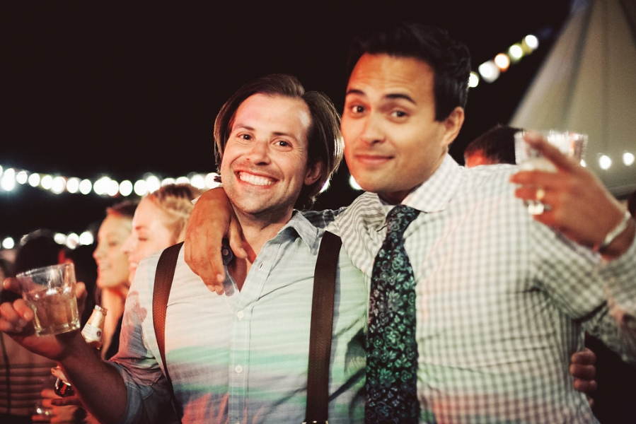 two_wedding_guests_holding_drinks_at_evening_reception.jpg