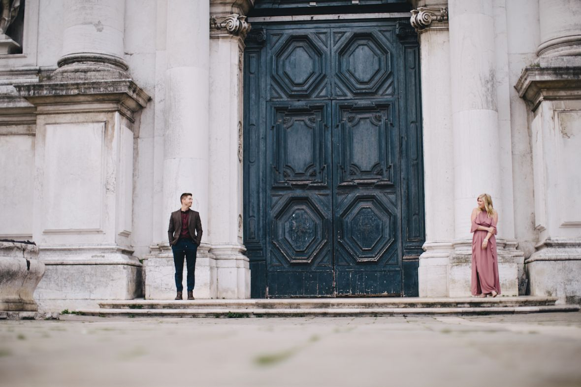 venice_engagement_couple_standing_on_either_side_of_giant_blue_door.jpg