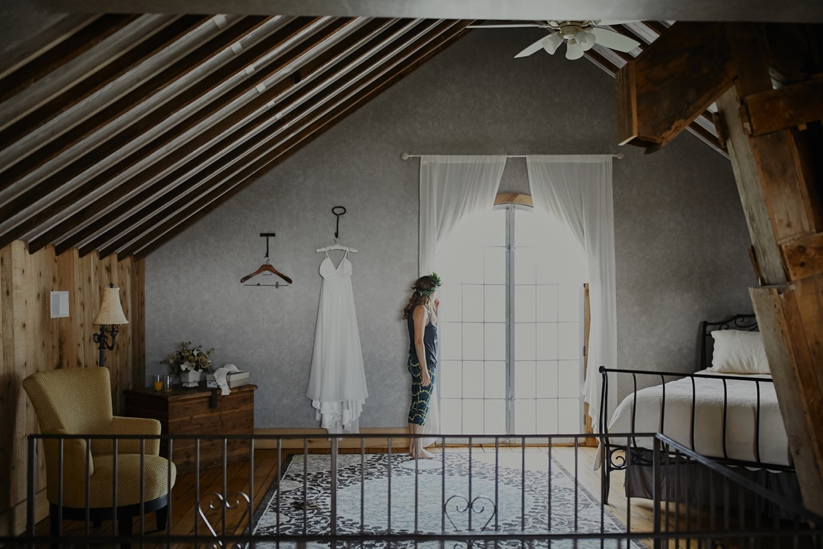 view_of_bridal_suite_dress_hanging_gray_wall_bride_looking_out_window.JPG
