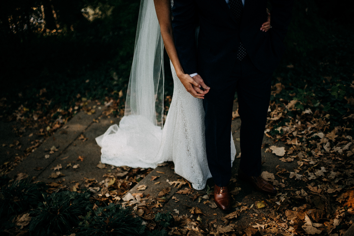 view_of_bride_and_groom_feet_on_leafy_park_ground.jpg
