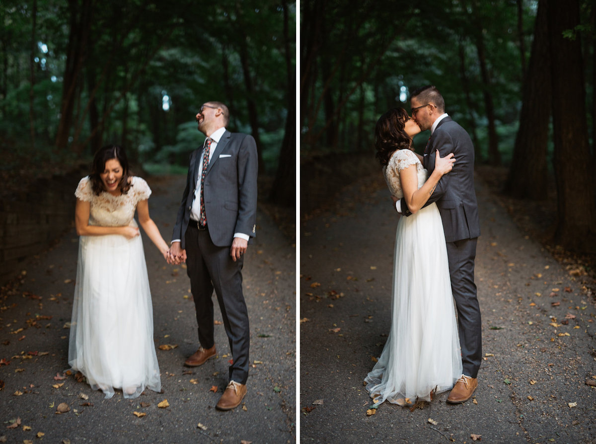 vintage_bride_and_Groom_walking_in_woods_on_path_laughing_and_kissing.jpg