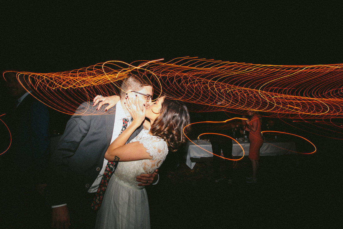 vintage_bride_and_groom_kissing_during_nighttime_wedding_reception_camera_flaires.jpg