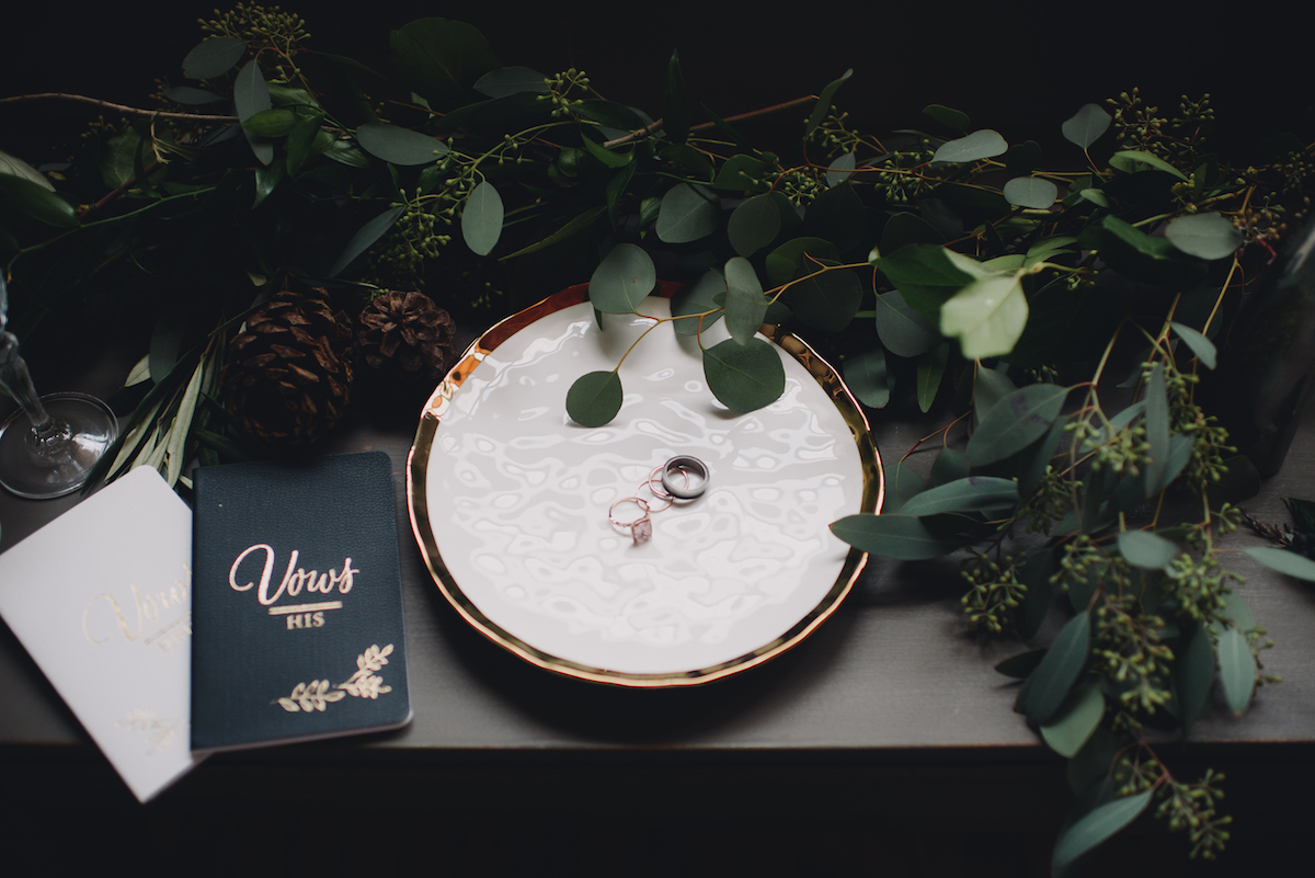 wedding_bands_on_marble_plate_with_vow_booklets_and_greenery.jpg