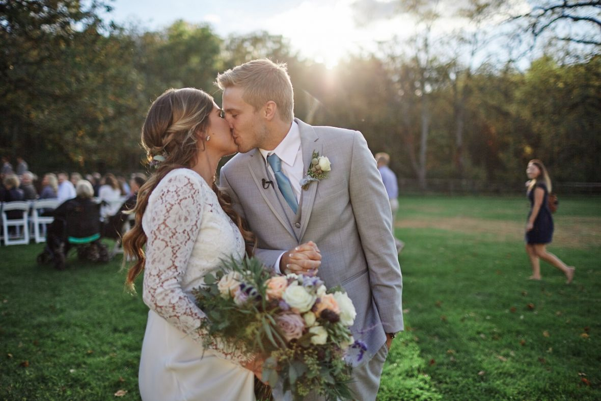 wedding_couple_kissing_in_sunlight_after_outdoor_ceremony.jpg
