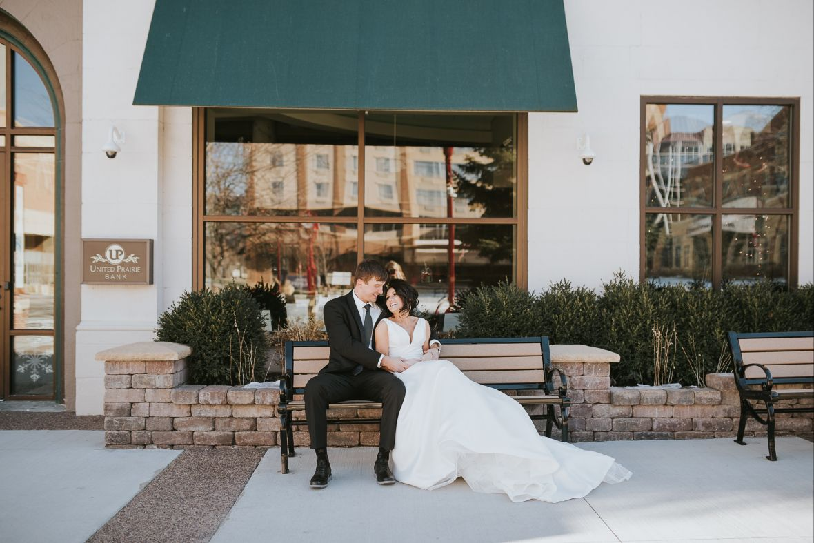 wedding_couple_sitting_on_bench_under_dark_green_awning.jpg