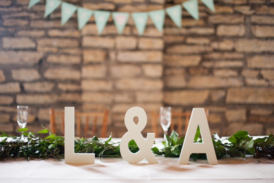 wedding_couples_initials_wooden_signs_on_reception_table_with_greenery_brick_wall.jpg