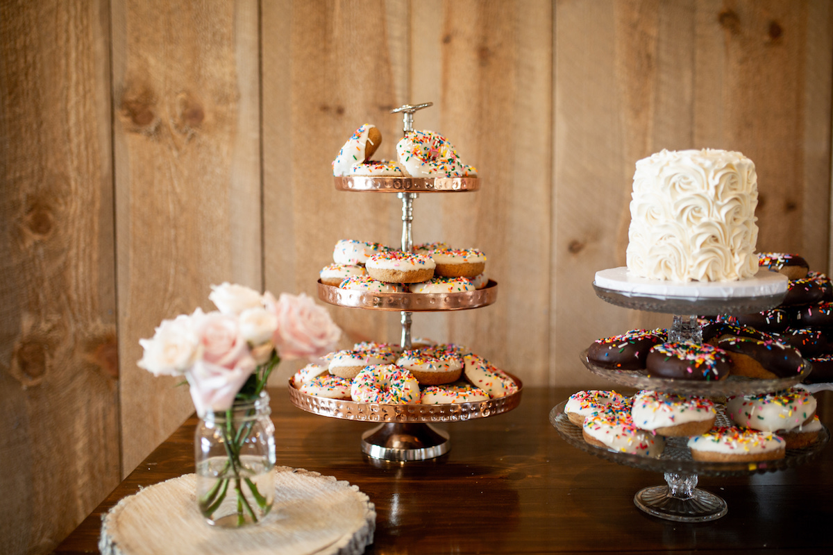 wedding_dessert_table_donut_tiers_white_flower_cake_pink_roses_wooden_walls.jpg