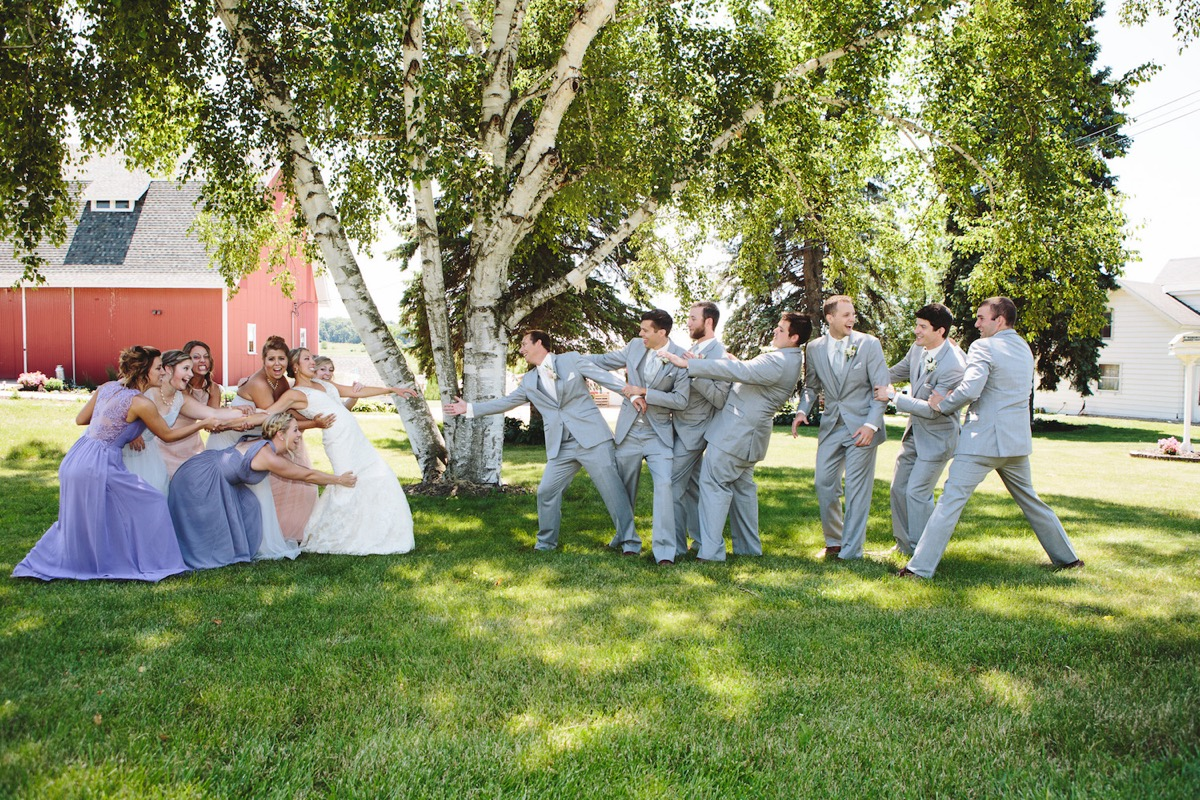 wedding_party_tugging_bride_and_groom_away_from_each_other.jpg