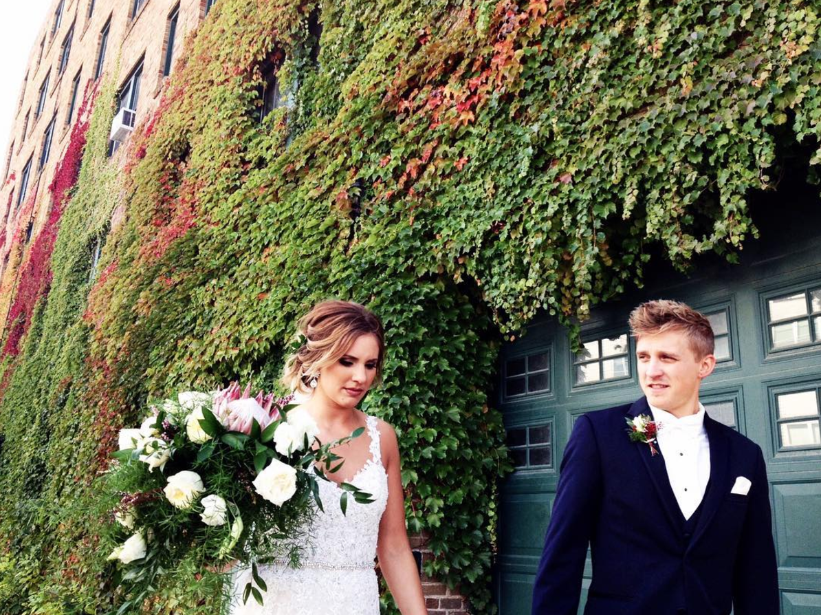 wedding_photo_of_newlyweds_outside_of_a_green_red_moss_covered_brick_building_minnesota_wedding_videography.png