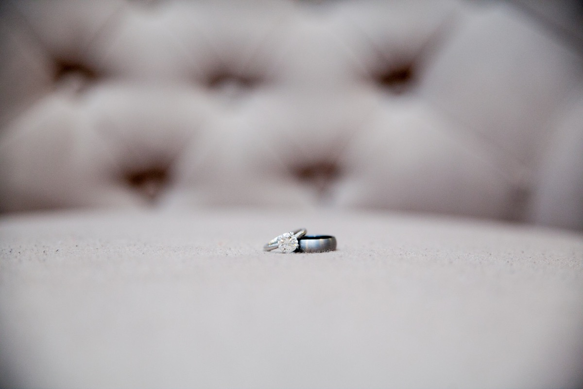 wedding_ring_and_band_closeup_on_beige_chair.jpg