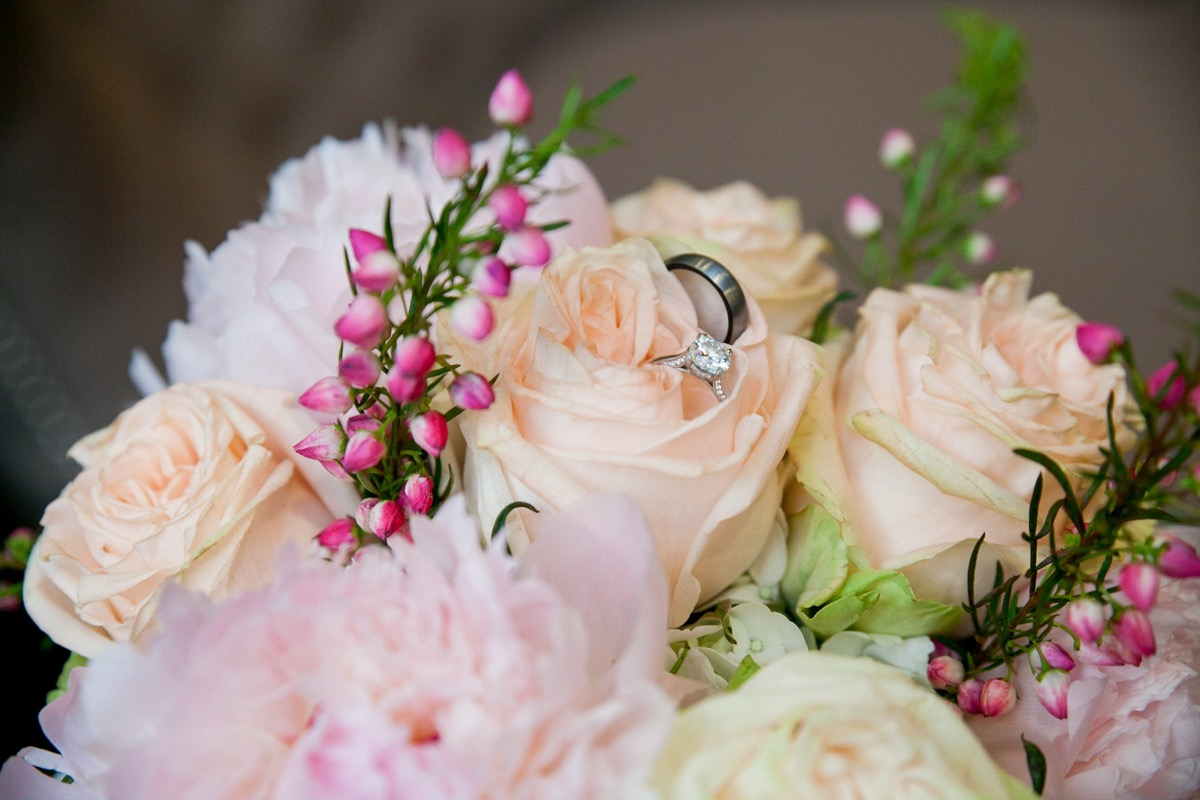 wedding_ring_and_band_sitting_on_light_coral_flower.jpg