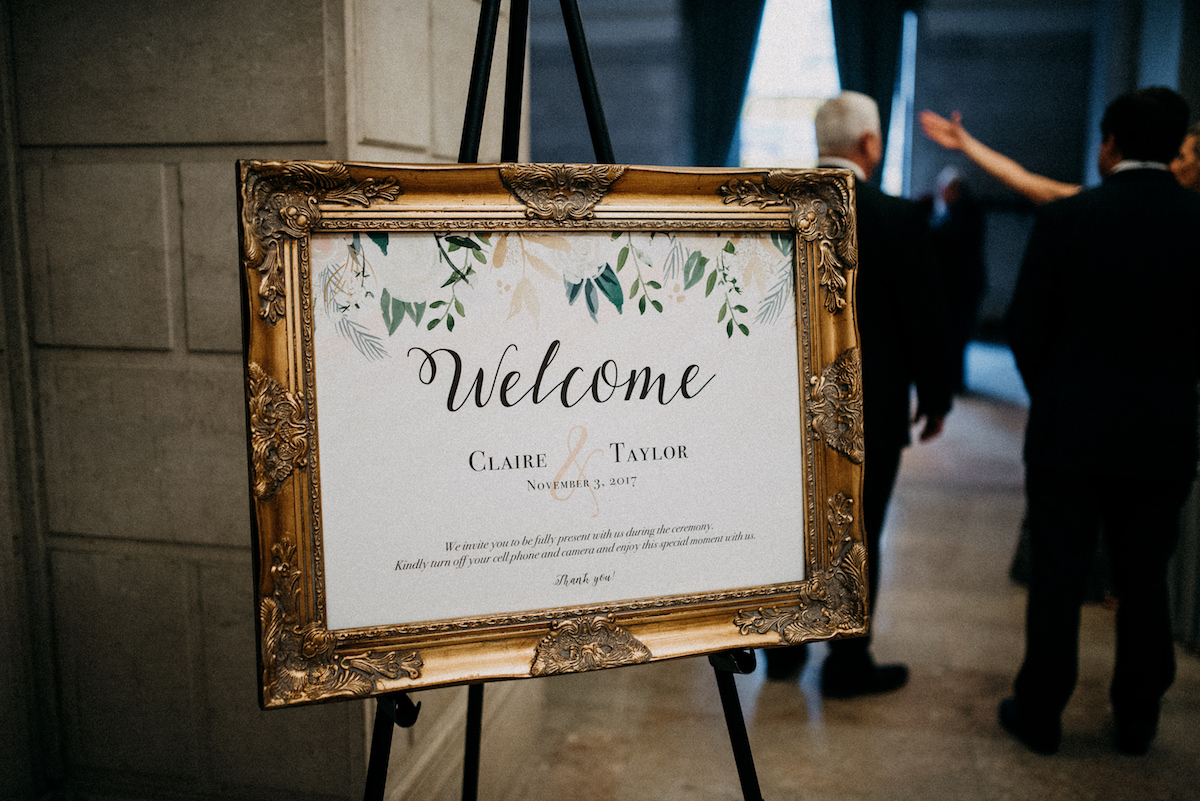 wedding_welcome_sign_gold_frame_in_city_building.jpg