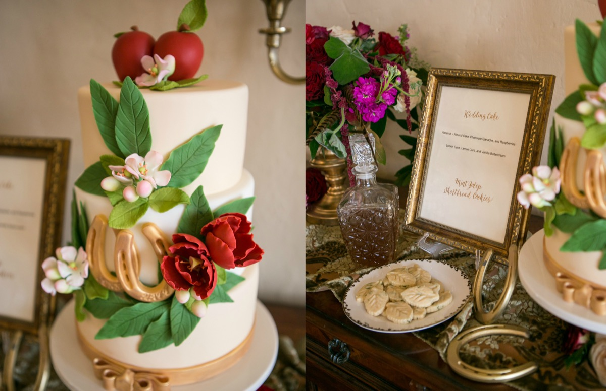 white_cake_with_gold_W_letter_greenery_red_flowers_red_apples_made_out_of_frosting_wedding_cake_sign_in_gold_frame.jpg