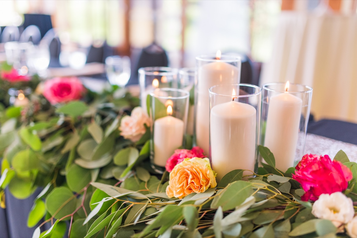 white_candles_on_top_of_table_greenery_orange_hot_pink_flowers.jpg