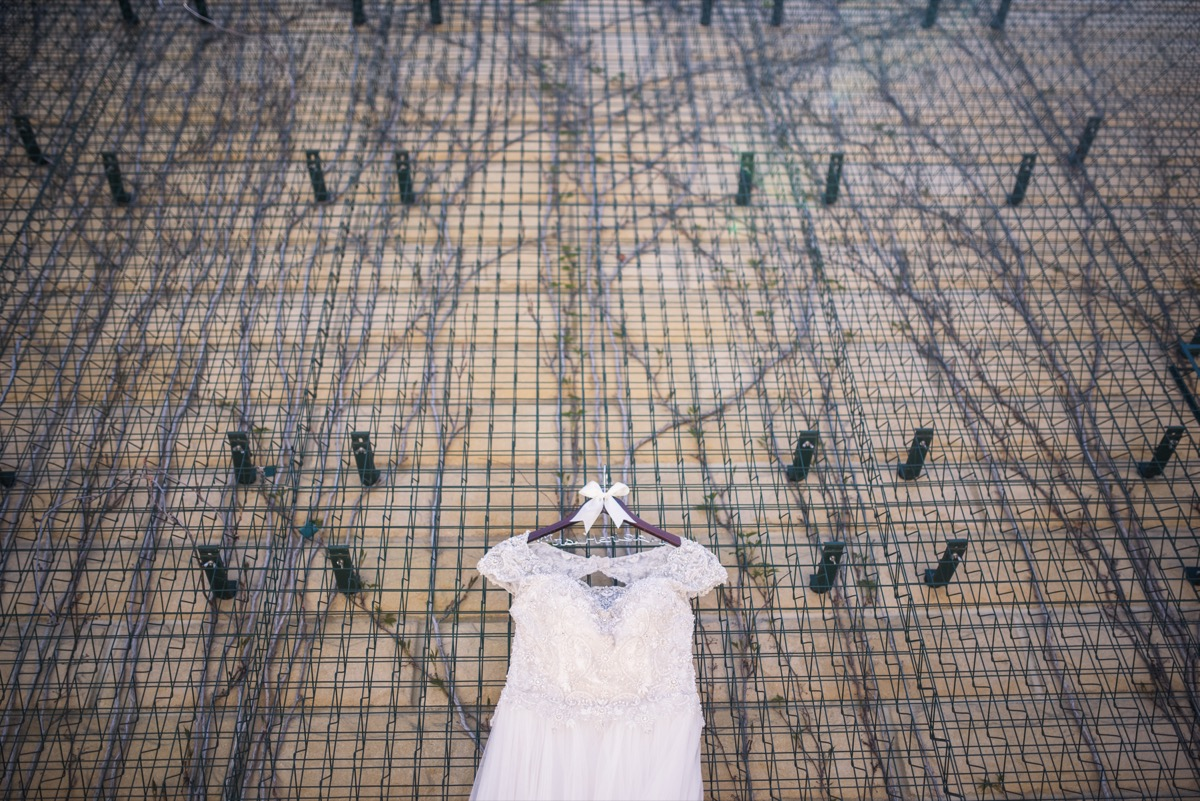 white_lace_dress_hanging_on_fence.jpg