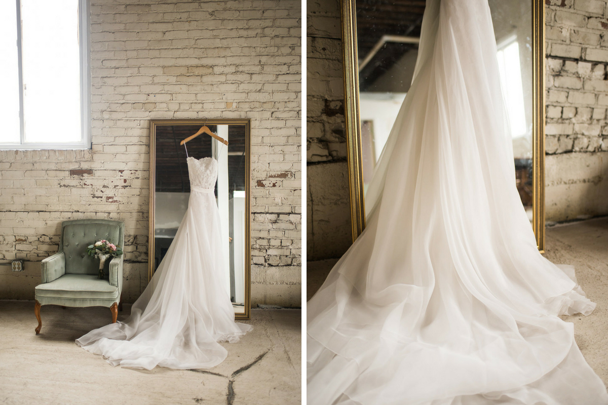 white_lace_tulle_wedding_gown_hanging_gold_mirror_green_chair_white_brick_wall.jpg