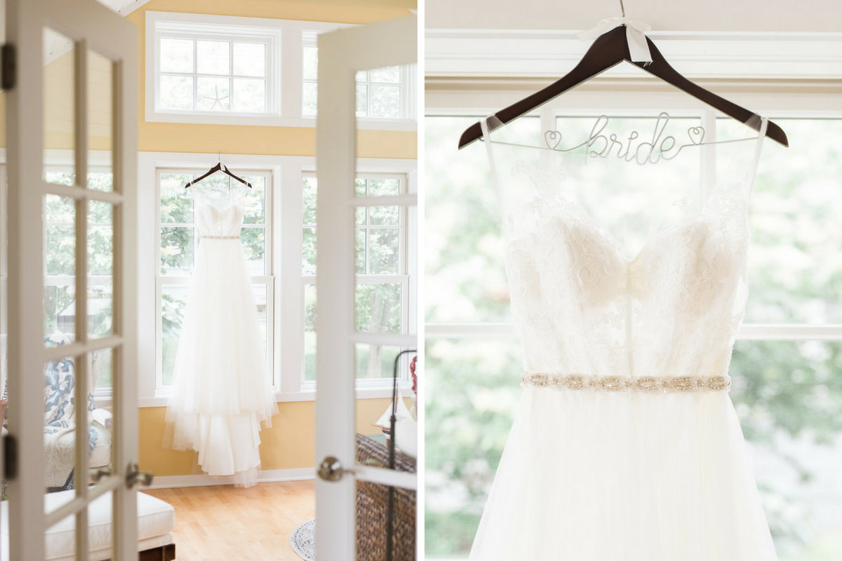 white_lacey_wedding_gown_hanging_in_front_of_bright_large_windows_yellow_walls.jpg