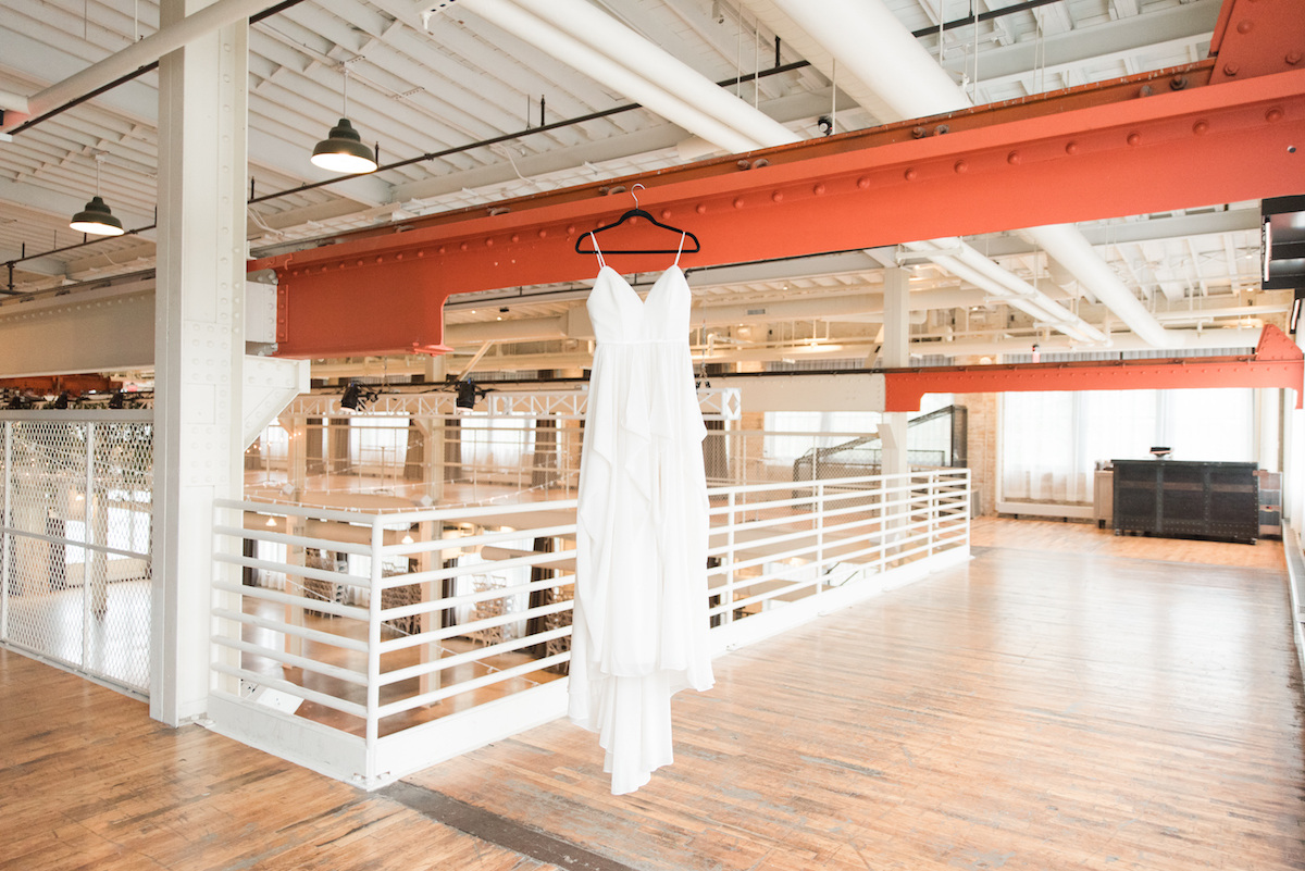 white_layered_wedding_gown_hanging_in_undustrial_style_wedding_venue.jpg