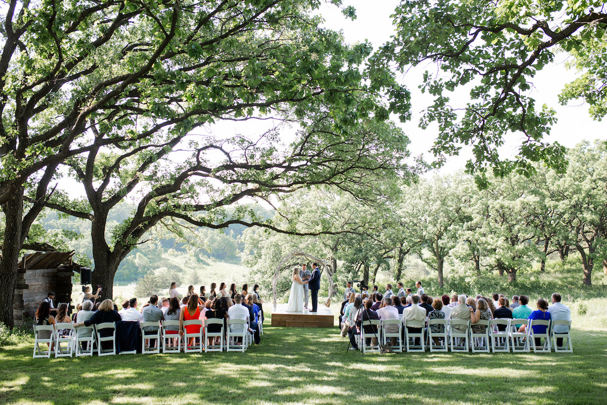 wide_view_of_outdoor_wedding_ceremony_large_green_trees_arching_over_bride_and_groom.jpg