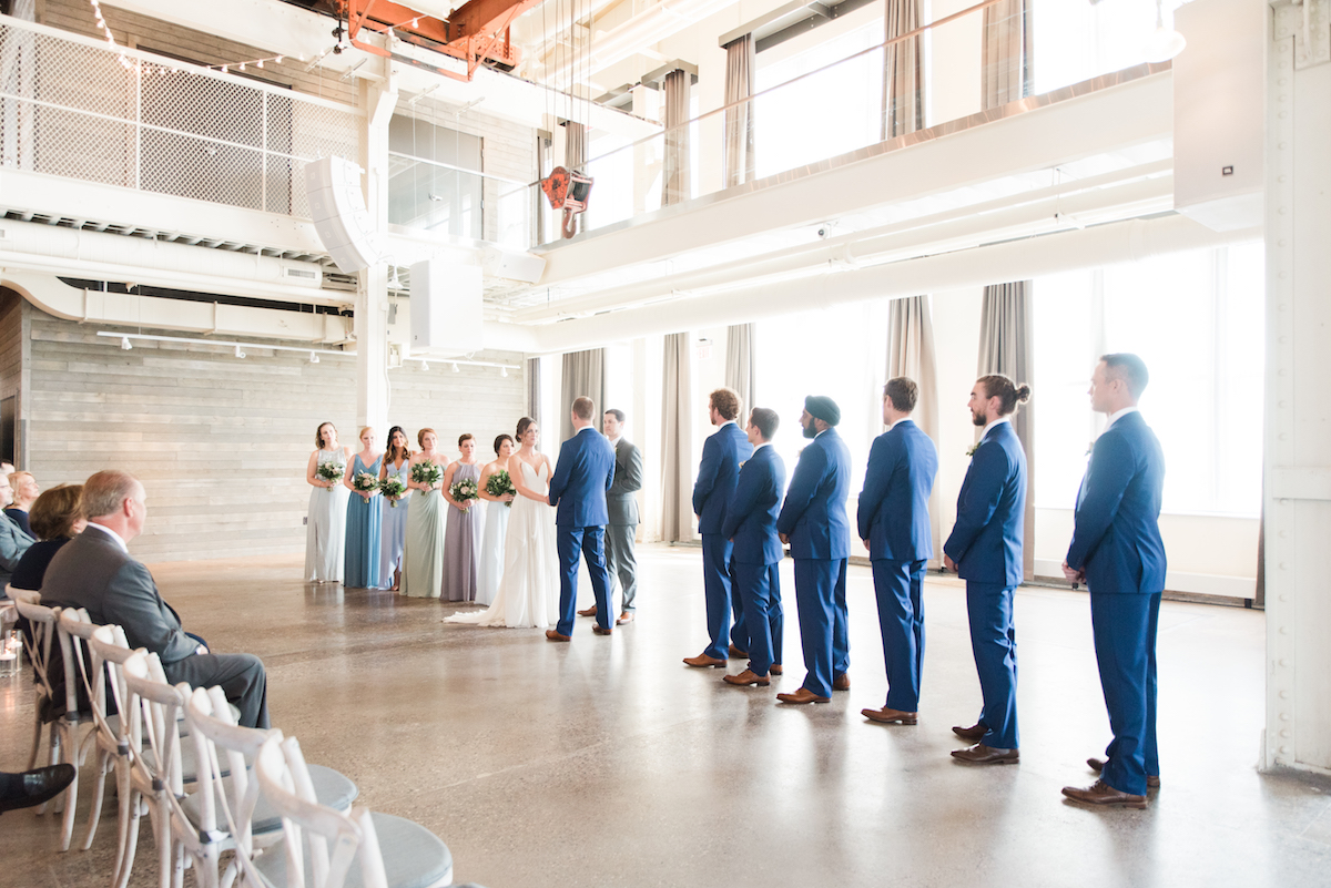 wide_view_of_wedding_ceremony_bride_and_groom_holding_hands_with_bridesmaids_and_groomsmen_standing_on_sides.jpg
