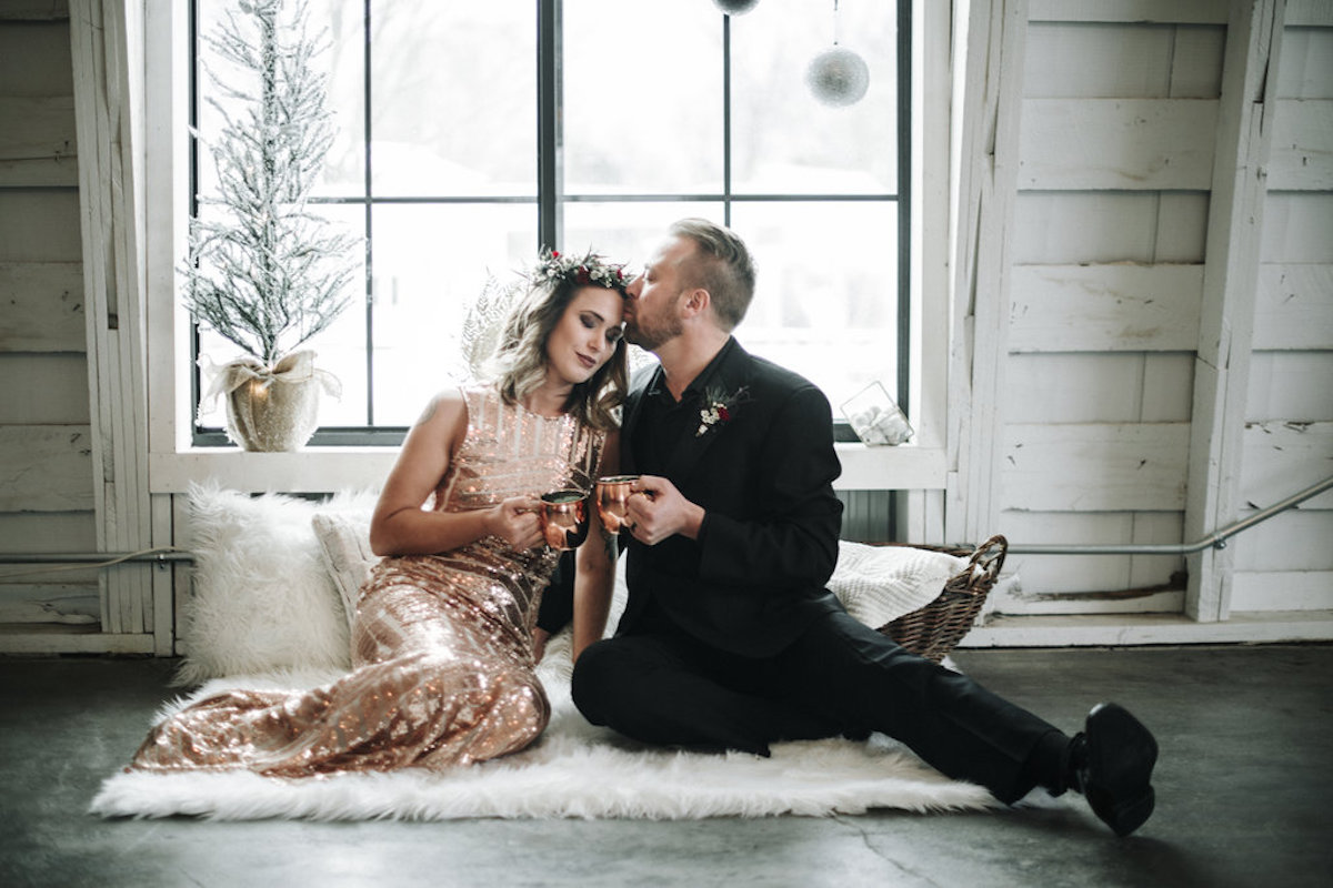 winter_boho_bride_and_groom_sitting_on_rug_with_drinks.jpg