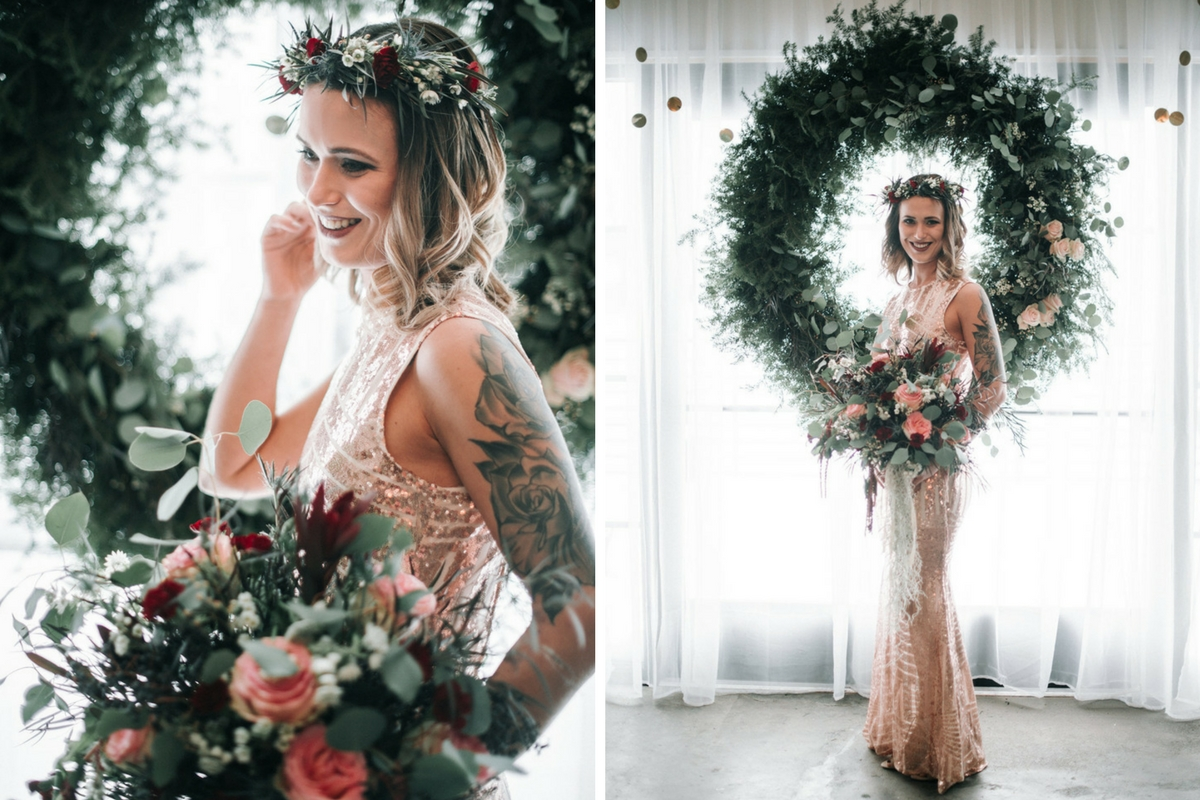 winter_boho_bride_standing_with_bouquet_with_large_green_wreath.jpg
