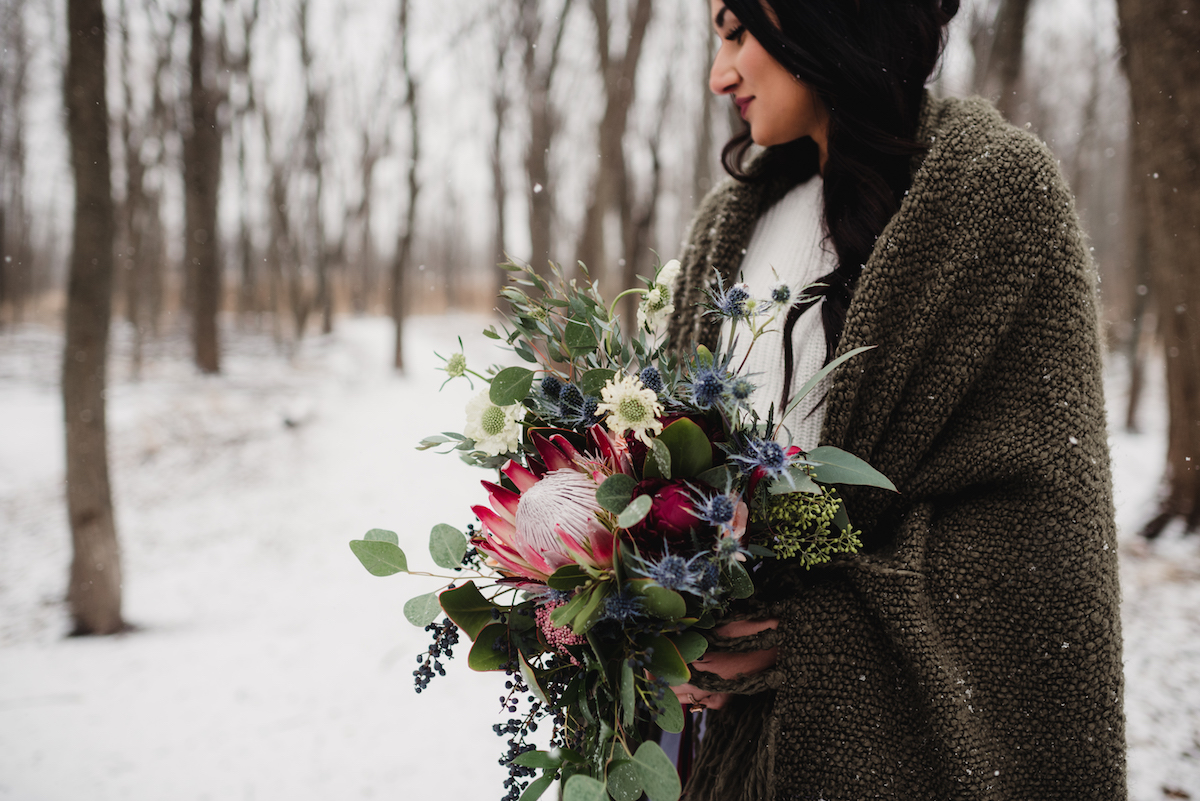 winter_bride_in_brown_cloak_holding_floral_bouquet.jpg