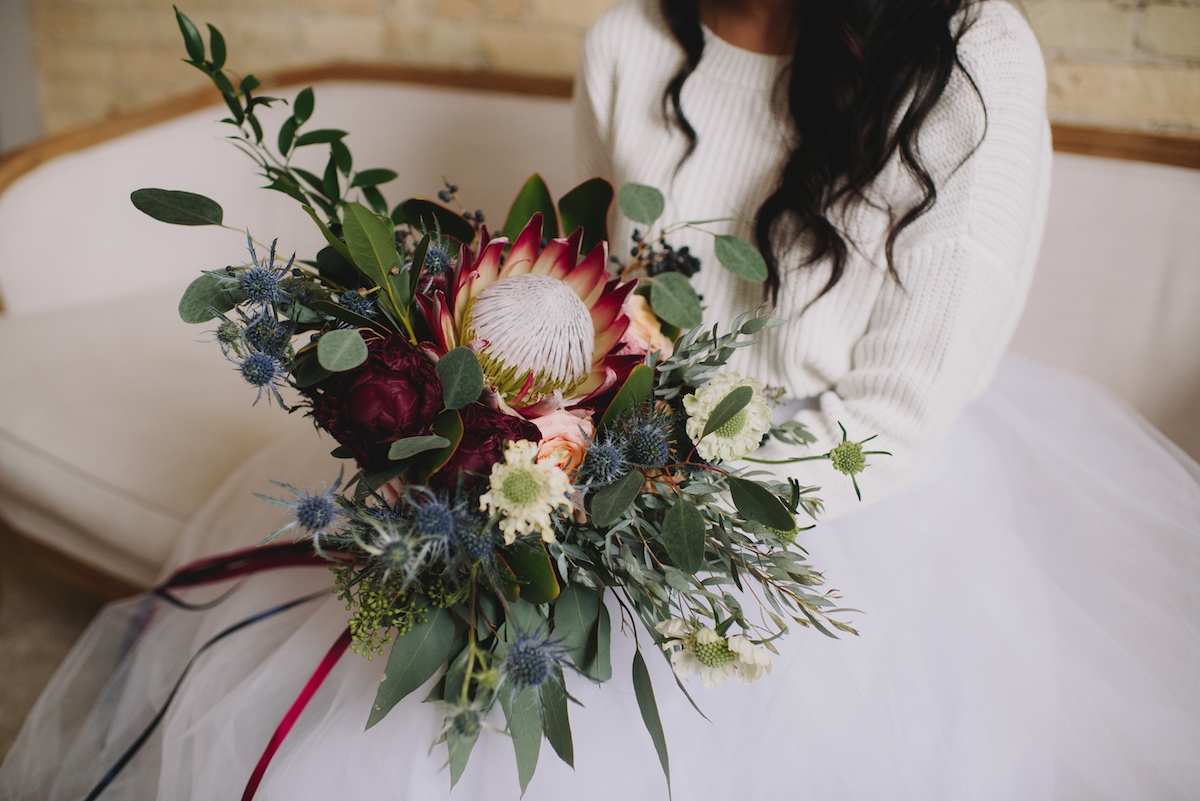 winter_bride_sitting_on_couch_with_large_woodsy_bouquet.jpg