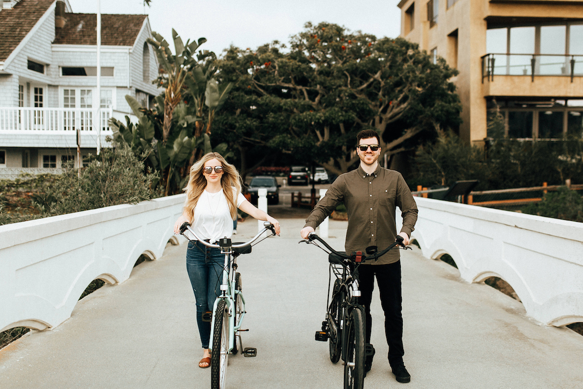 woman_and_fiance_walking_bikes_on_small_white_bridge.JPG