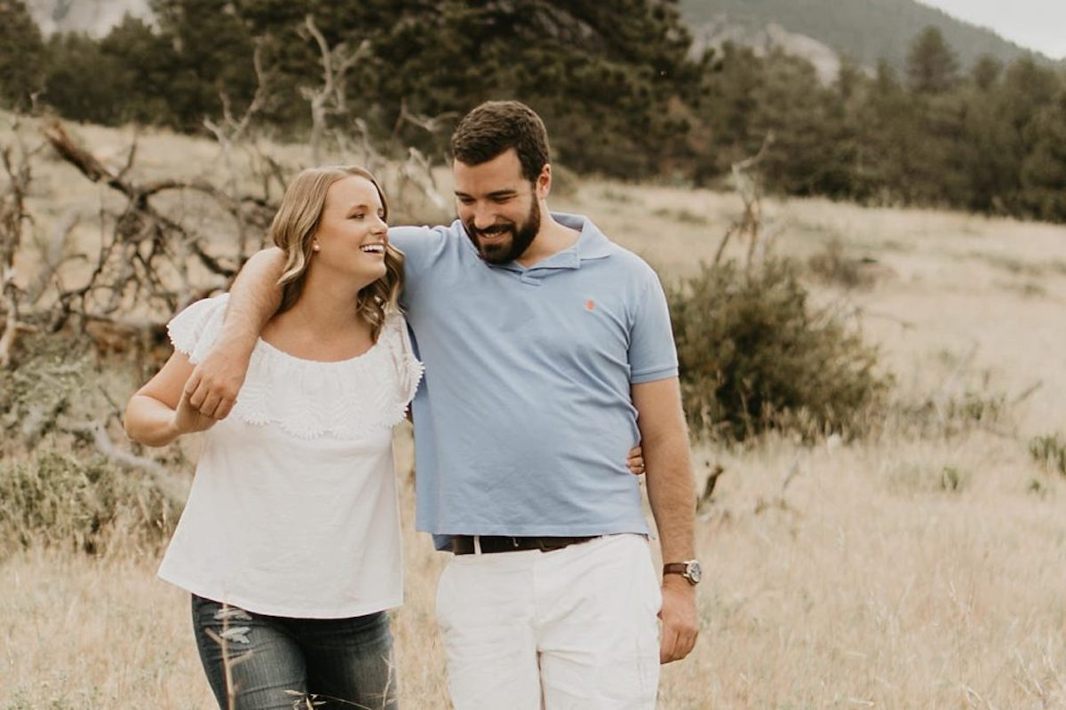 woman_and_fiance_walking_in_grassy_Colorado_field_arms_around_eachother_laughing.jpg