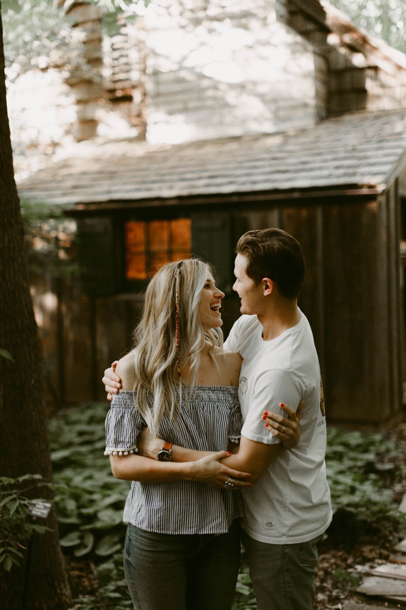 woman_and_man_laughing_brown_cabin_behind.jpg