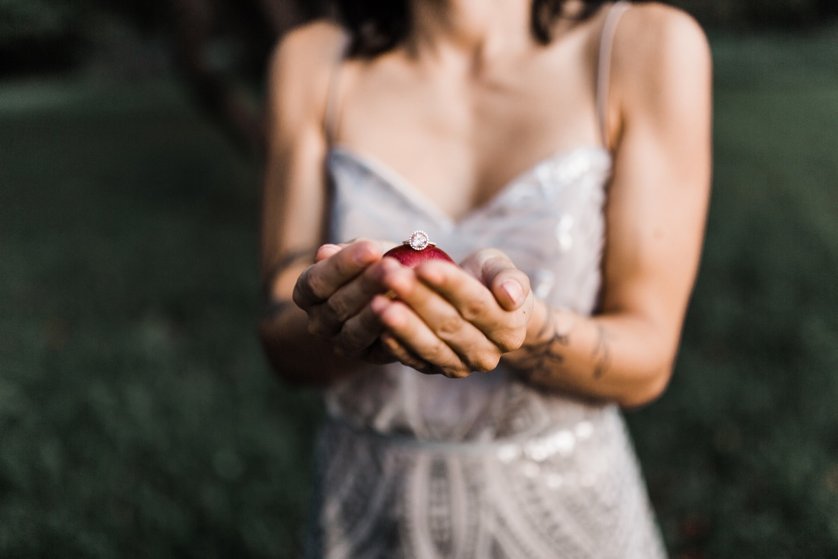 woman_holding_round_engagement_ring_on_apple.jpg
