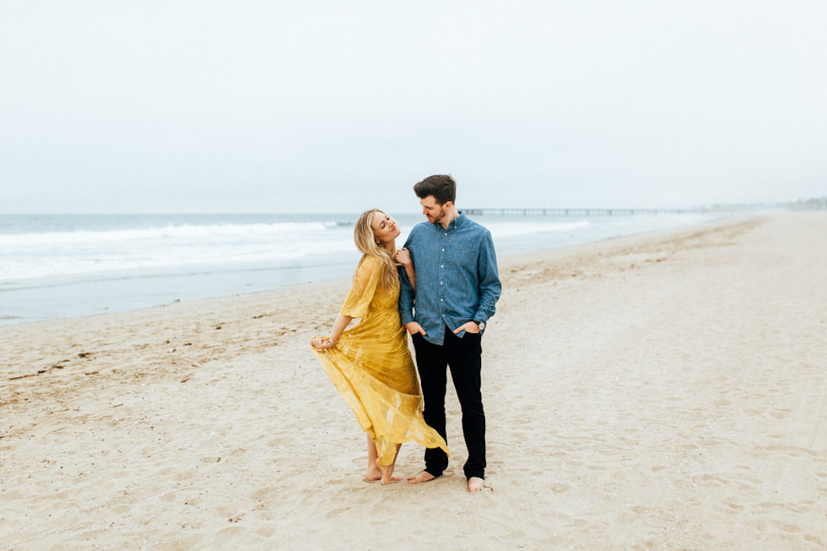 woman_wearing_yellow_dress_blowing_in_wind_with_fiance_standing_by_ocean.JPG
