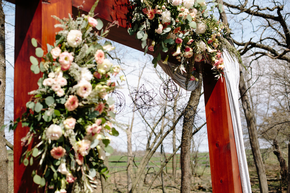 wooden_arch_pink_white_floral_hanging_decor_in_woods.jpg