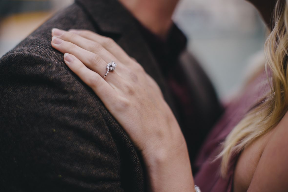 zoomed_in_shot_of_engagement_ring_placed_on_brown_suit_jacket.jpg