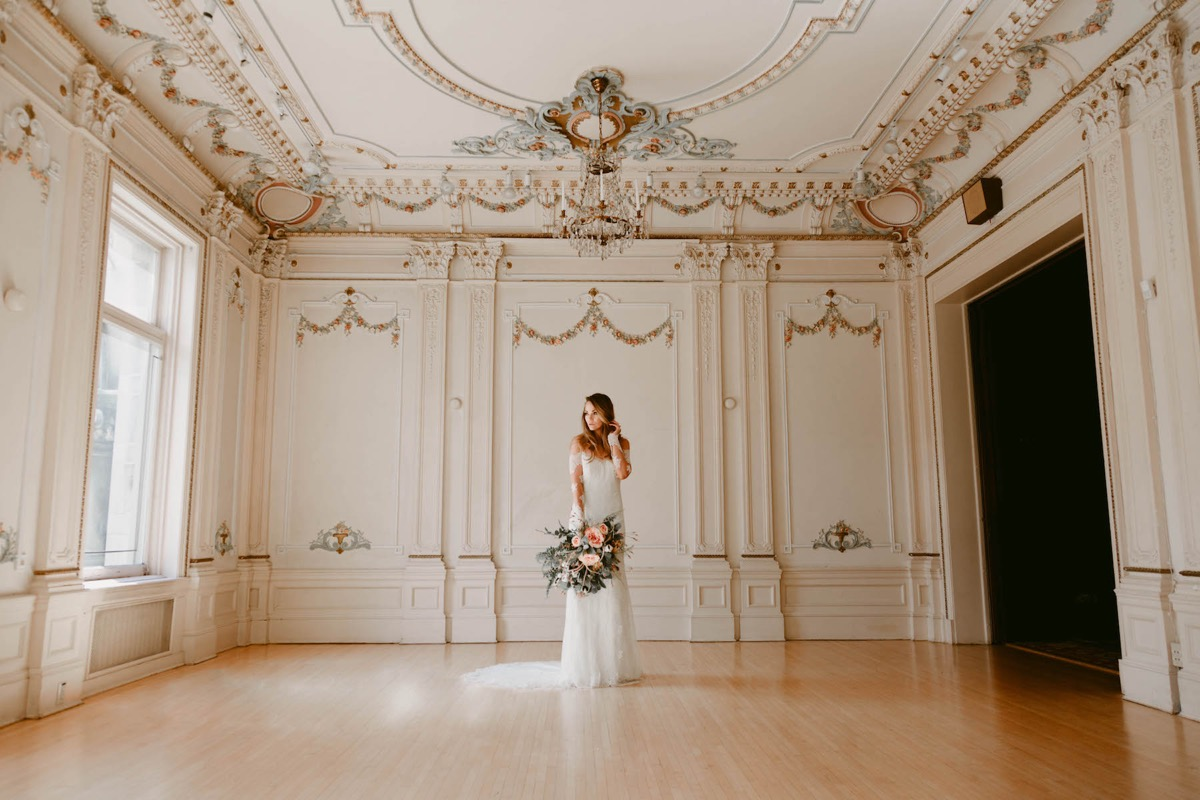 zoomed_out_photo_of_bride_looking_to_side_vintage_room.jpg